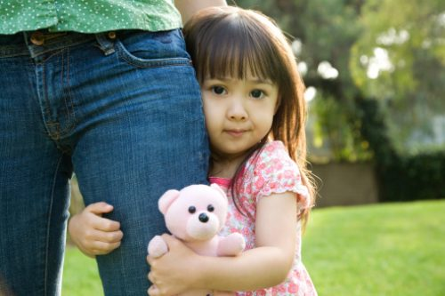Three year old girl clinging to mother's leg
